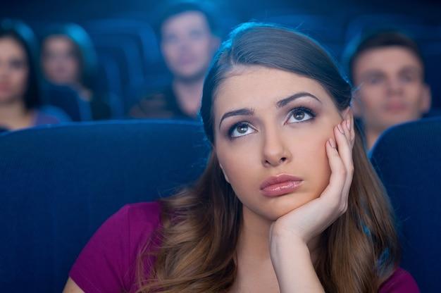 Смотрю скучный фильм. скучно молодая женщина, взявшись за подбородок во время просмотра фильма в кинотеатре