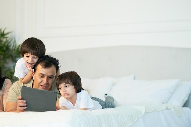 만화를 보고 있다. 디지털 태블릿을 사용하여 귀여운 작은 아들들과 함께 침대에 누워 있는 행복한 라틴 아빠. 아침에 만화를 보면서 화면을 보는 아버지와 아이들