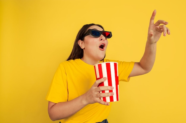 Watching cinema in 3d-eyewear with popcorn. caucasian woman on yellow studio background. beautiful brunette model in casual style. concept of human emotions, facial expression, sales, ad, copyspace.