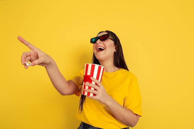 ポップコーンを使った3dアイウェアで映画を見る。黄色の壁に白人女性。カジュアルなスタイルの美しいブルネットモデル。人間の感情、表情、販売、広告、コピースペースの概念。