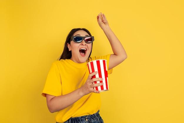 ポップコーンを使った3dアイウェアで映画を見る。黄色の壁に白人女性。カジュアルなスタイルの美しいブルネットモデル。人間の感情、顔の表情、販売、コピースペースの概念。