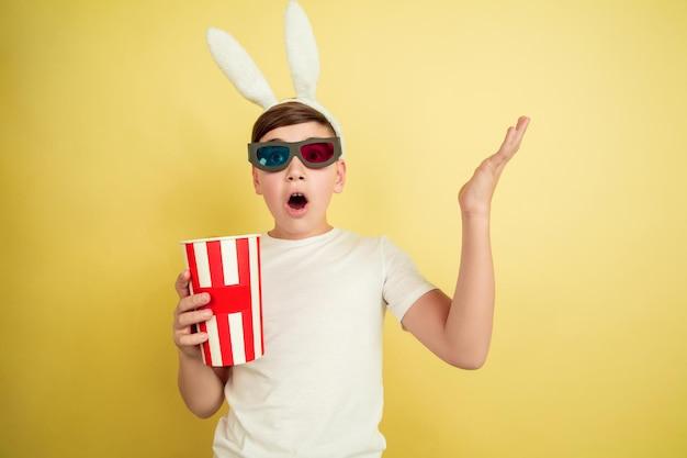 팝콘으로 안경을 쓴 영화관. 노란색 배경에 부활절 토끼로 백인 소년. 행복한 부활절.