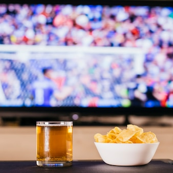Watching football concept with beer and chips