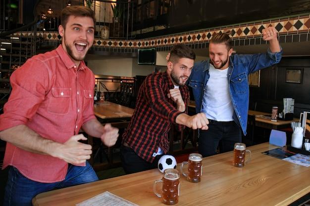 바에서 축구 관람. 맥주를 마시고 좋아하는 팀을 응원하는 행복한 친구들, 승리를 축하합니다.