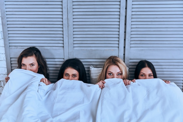 Watching horror movie.  top view of four beautiful young women covering face with white blanket and looking at camera while lying in the bed
