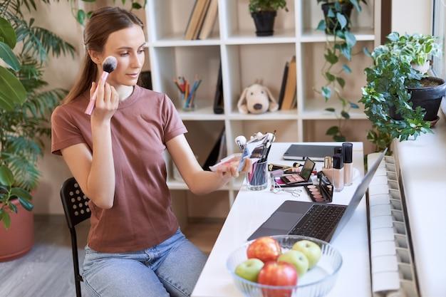 化粧チュートリアルをオンラインで見てカジュアルな服を着た若い美しい女性が使用して化粧を適用します