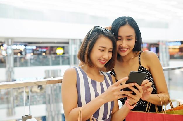ショッピング後に携帯電話で写真を見る