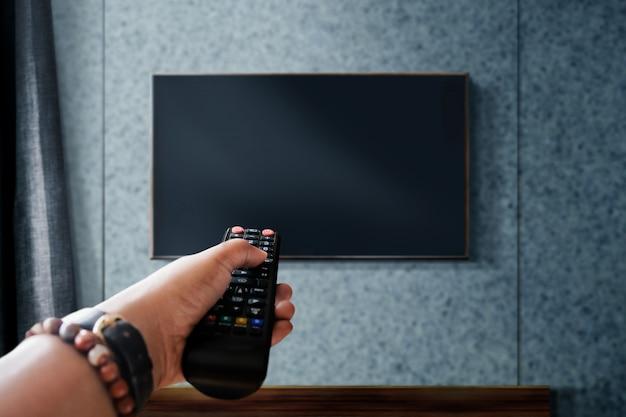 テレビのコンセプトを見ています。テレビのリモコンを持っている、またはチャンネルを変更している手