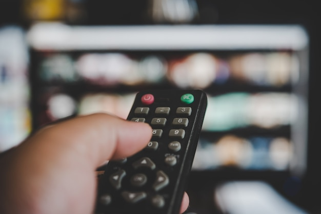 Watching  television, with a tv remote control in the hand