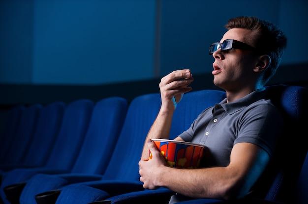 입체 영화를 보고 있습니다. 영화관에 앉아 팝콘을 먹고 영화를 보는 3차원 안경을 쓴 흥분한 청년