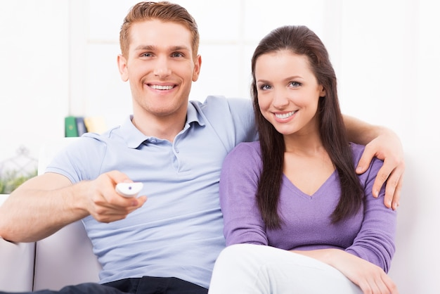 함께 tv를 봅니다. 쾌활한 젊은 남자와 여자는 소파에 함께 앉아있는 동안 tv를보고