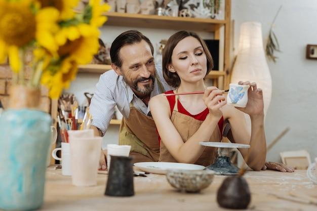 妻を見ています。土鍋を飾る彼の魅力的な陽気な妻を見ているハンサムなひげを生やした男の笑顔