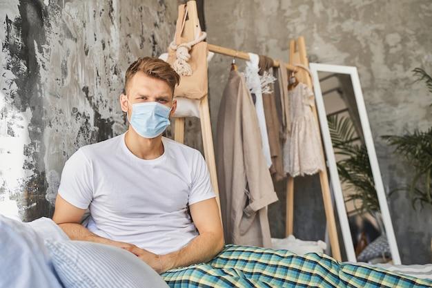 貴方を見てるよ。ベッドに座って、自宅隔離中に医療用フェイシャルマスクを着用している親切な男性