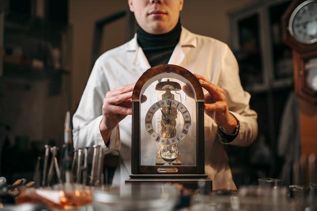 Часовщик, держащий старые настольные часы. ремонт старинных механических часов в мастерской