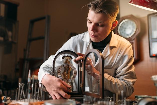 오래 된 테이블 시계를 들고 시계