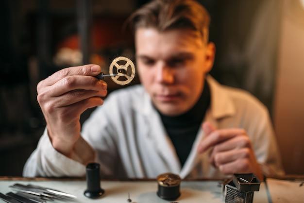 시계 장인이 핀셋으로 오래 된 기어를 들고 있습니다.