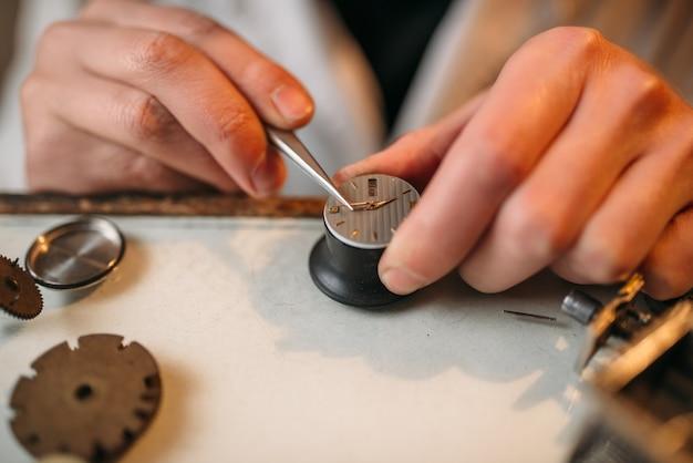 Watchmaker repair broken clockwork with tweezers