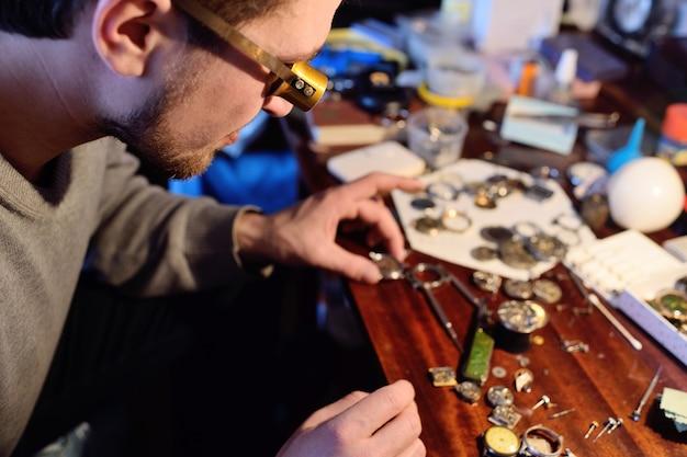 Watchmaker repairing clockwork
