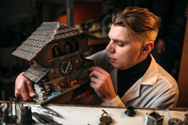 시계 제작자는 목조 주택의 형태로 오래된 벽시계를 복원
