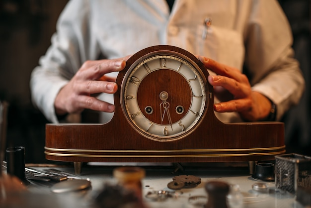 Watchmaker restore old wooden table clock