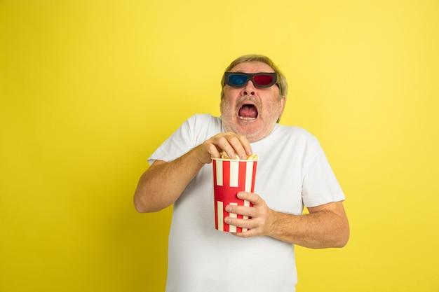 Guardare il cinema con popcorn e occhiali 3d. ritratto di uomo caucasico su sfondo giallo studio. bellissimo modello maschile in camicia.