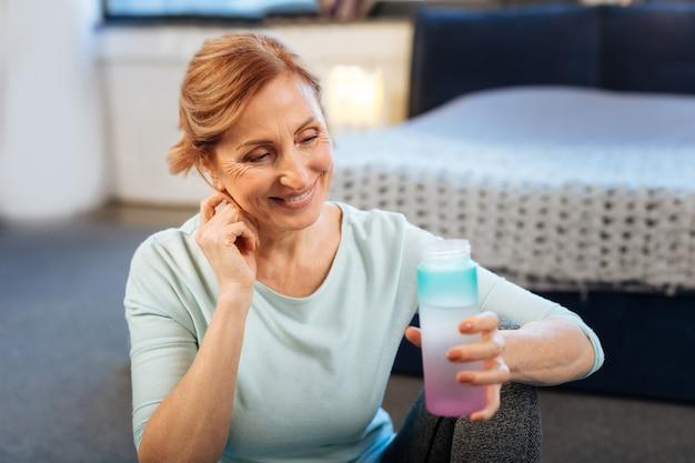 トレーニング後の水。プラスチック製の水筒を持っている間彼女のあごに触れている結ばれた髪を持つ快適な成熟した女性