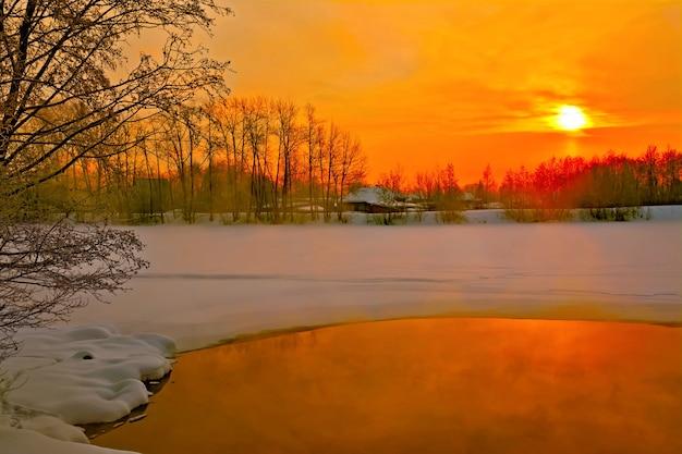 川の水と氷、木々、夕焼け空を背景に木造住宅