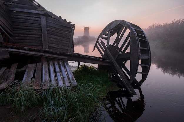 Деревянная мельница воды и мельницы на реке рано утром на рассвете в традиционной русской деревне. сельский осенний пейзаж с первыми заморозками