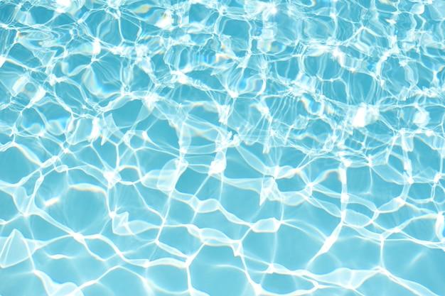 水の背景、波のテクスチャと波紋と流れ。夏の青いプールのパターン。