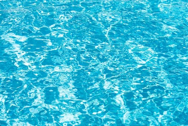 水の背景、波紋。青いスイミングプールのパターン。海面。太陽の反射とプールの水。コピースペース付きのバナー。