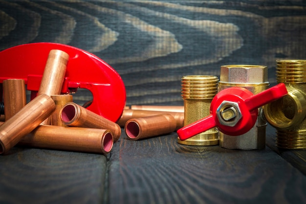 Water ball valve with red handle and copper pipes for plumbing repairs on black wooden boards