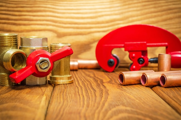 Water ball valve with red handle and copper pipes for plumbing repairs on vintage wooden boards