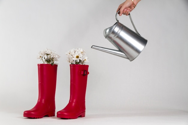 Water boots next to a hand with a watering can