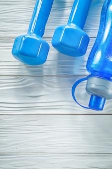 Бутылка воды синие гантели на деревянной доске фитнес-концепции