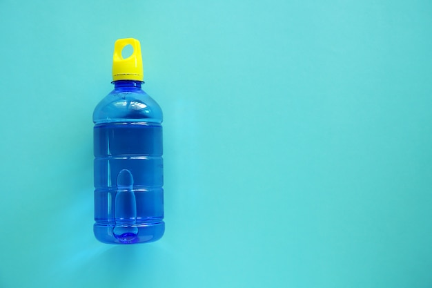 Water bottle on blue with copy space for healthy drinking concept