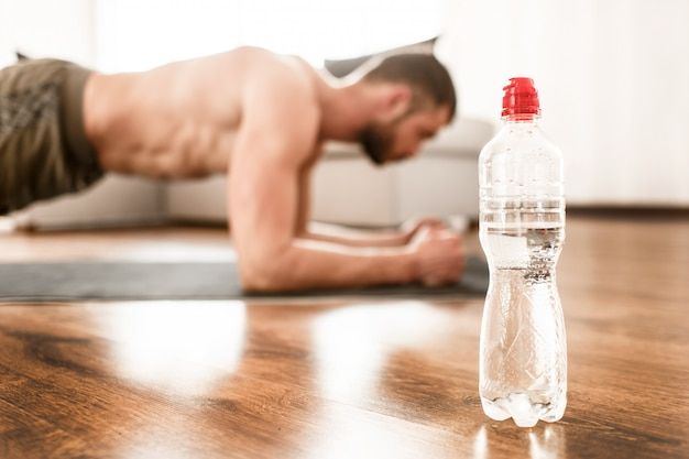 Water bottle close-up. young man doing sport at home. cut view of t-shirtless guy sportsman with a sports figure  in plank position.