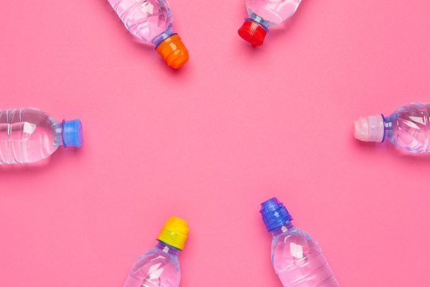 Water bottle flat lay top view on color paper background