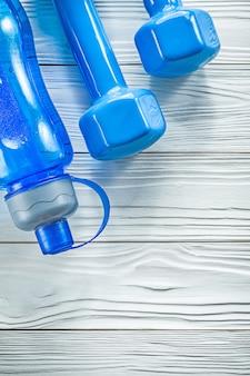 Бутылка с водой для легкой атлетики синие гантели на деревянной доске концепции спортивной тренировки