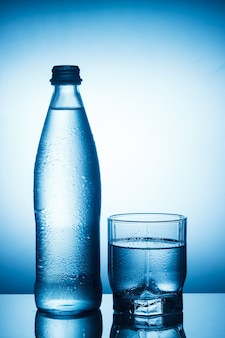 Water bottle and glass on blue background