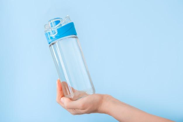 파란색 배경에 스포츠를 위한 여성 손 재사용 가능한 식수 스포츠 병에 물병