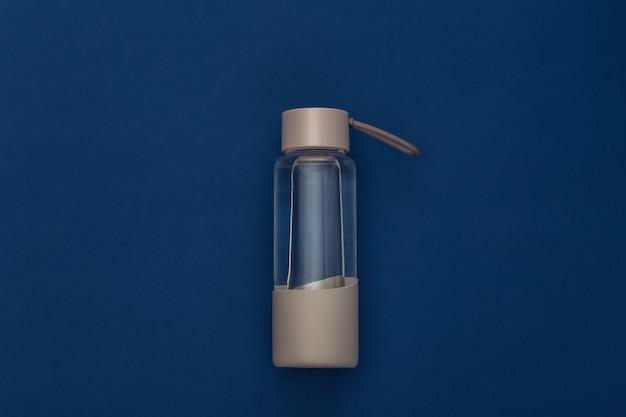 古典的な青い背景の上の水のボトル。健康的なライフスタイル、フィットネストレーニング。カラー2020。上面図