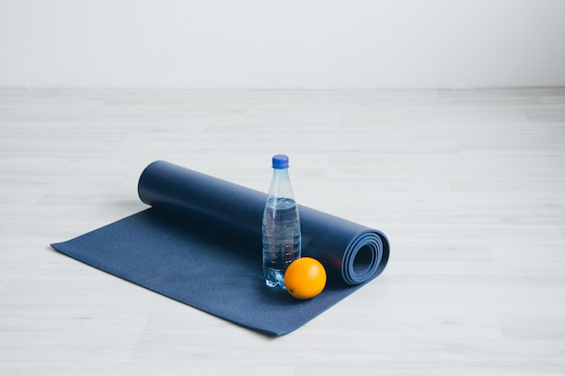 Water bottle, orange, and yoga mat.