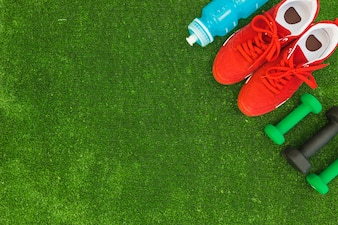 Water bottle; red sport shoes and dumbbells on green turf