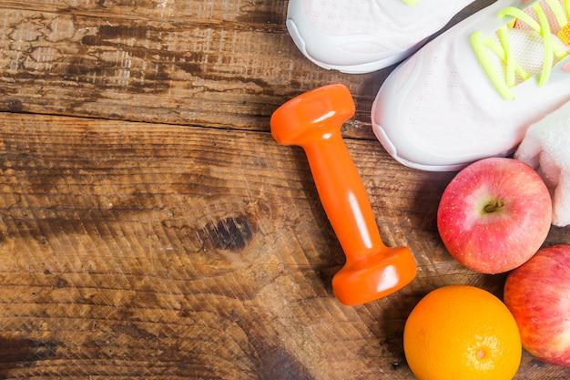 Bottiglia di acqua con scarpe da ginnastica e pesi