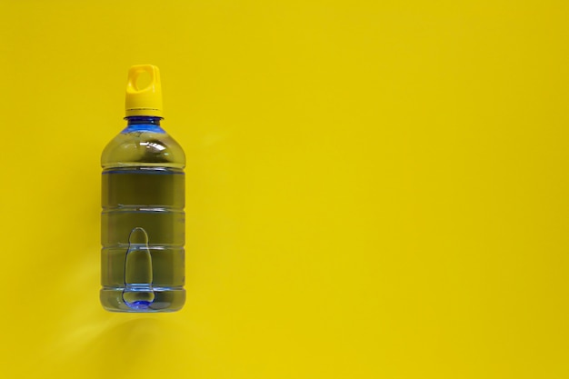 Water bottle on yellow copy space for healthy drinking concept