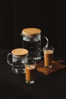 Бутылки с водой и кофейные стаканы на темном фоне