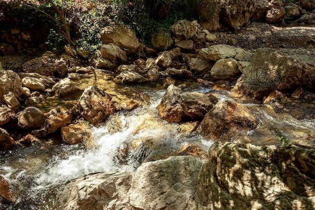 Вода пробивается сквозь камни, вид на водопад. красочная природа, тропинка, отдых.