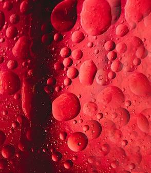 赤い背景の上に抽象的な方法で均等に配置された水の泡。