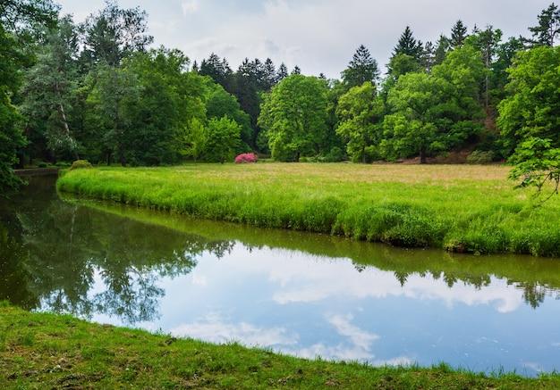 Водный канал на травянистом лугу в летнем городском парке