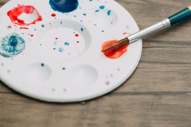 水彩画と混合色のプレートとペイントブラシは、紙にアートを描くために木製のテーブルに置かれます。